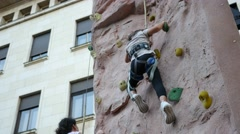 People kids and adults climb the climbing wall on a street cultural sport fest Stock Footage