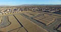 Aerial over desert reveals housing tracts and empty lots in the desert. Stock Footage