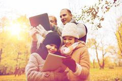 Happy family with tablet pc in autumn park Stock Photos