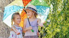 Two girls 4 and 6 years of hiding under colorful umbrellas. Warm summer rain Stock Footage
