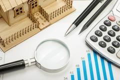Model house, construction plan for building, magnifying glass, divider compass Kuvituskuvat