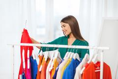 happy woman choosing clothes at home wardrobe - stock photo
