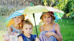 Three cheerful carefree girl under the umbrella of the rainbow colors. There is Stock Footage