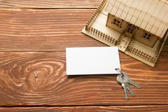 Real Estate Concept. Model house, keys, blank business card on wooden table. Top Stock Photos