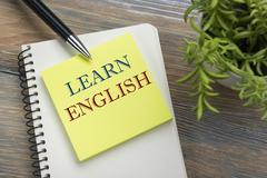 Learn English Text written on notebook page, red pencil and coffee cup. Office Stock Photos
