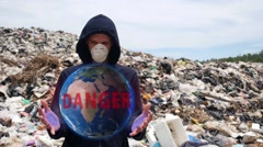 Man with Hologram Planet Earth in Garbage. Pollution Stock Footage