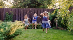 Carefree fun children play in the garden. Laughing, running under the jets of Stock Footage