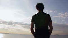 A young indian look man standing on the stone beach looking forward on the sea Stock Footage