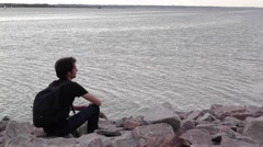 A young indian look man sitting on the stone beach looking forward on the sea Stock Footage