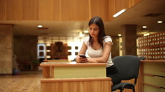 pretty woman surfing the net on smartphone in a library 2 - stock footage