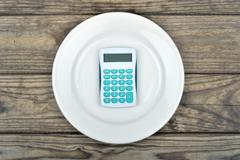 Plate with hand calculator on wooden table Stock Photos
