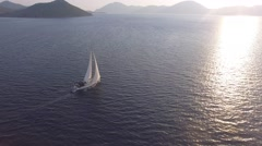 Aerial View of A Bare Boat Sailing into the Sun in Mediterranean Sea Stock Footage