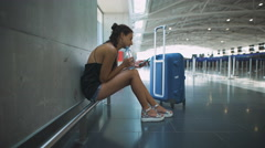 Passenger, woman siting in the airport, waiting for her flight using her phone Stock Footage