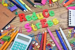 Reduce Stress text and office tools on wooden table Stock Photos