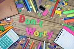 Don't Worry word and office tools on wooden table Stock Photos