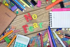 Fear word and office tools on wooden table Stock Photos