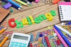 Challenge word and office tools on wooden table Stock Photos