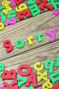 Sorry on wooden table Stock Photos
