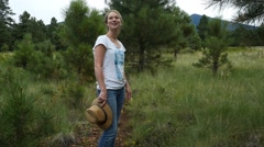 A happy girl hiking in a forest meadow Stock Footage