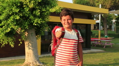 Portrait of a schoolboy with backpack smiling to a camera Stock Footage