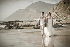 Attracting young couple newly weds walking on rocky beach Stock Photos