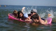 Family having fun playing on inflatable mattress Stock Footage