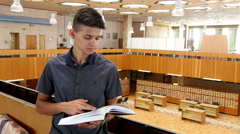 4k, handsome boy reading a book in the library 2 Stock Footage