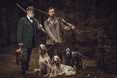 Two hunters with dogs and shotguns in a traditional shooting clothing, posing on Stock Photos