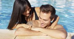 Smiling man with tattoo is cuddled by girlfriend Stock Photos