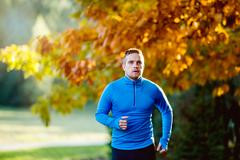Young handsome athlete running outside in sunny autumn nature Stock Photos