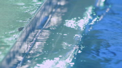 Water filtration system in swimming pool. Water surface near side of pool Stock Footage