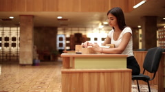 Pretty girl looking on catalog on the table in a library 1 Stock Footage