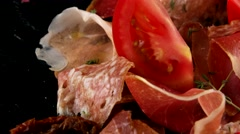Assorted meats (ham, salami, bacon) and tomatoes, closeup Stock Footage