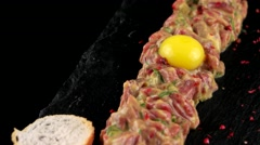 Beef tartare with egg yolk on the black stone board Stock Footage