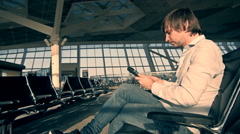 Handsome smiling man holding tablet and working at the airport, technology Stock Footage