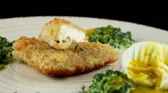 Roasted pikeperch fillet with soft poached egg and spinach, closeup, loop Stock Footage