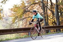 Young sportsman riding his bicycle outside in sunny autumn natur Stock Photos