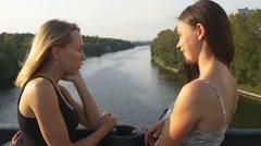 Girlfriends talking on a bridge Stock Footage