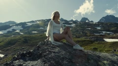A young girl, with beautiful legs, sits on the mountain peak. Stock Footage