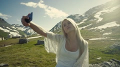 Taking selfie, making peace on the mountains hill, bright sunshine Stock Footage