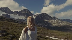 A girl is walking in the Alps mountains, the video is shot under unusual angle. Stock Footage