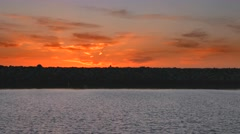 Person walks across rock wall and beautiful sunset horizon 2 - stock footage