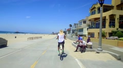 Woman rides bike alongside beach homes and beach on sunny day - stock footage