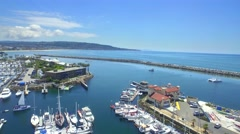 Aerial view of boats docked by mainland and mountains in horizon 2 Stock Footage