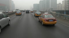 Traffic on a Beijing street, Smog is heavy as cars proceed on an 8 lane highway. Stock Footage
