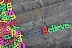 Believe on wooden table Stock Photos