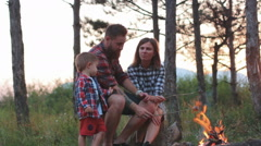 Young family outdoors to cook over a campfire marshmallows Stock Footage