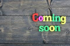 Coming Soon on wooden table Stock Photos