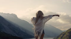 Girl in stylish jeans shorts is standing on the top of the mountain, moving Stock Footage