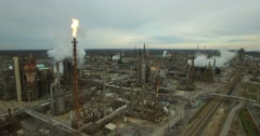 Excellent aerial over huge industrial oil refinery with gas torch burning. Stock Footage